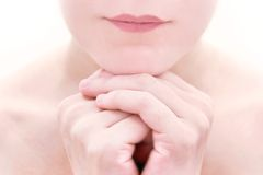 Close up of female lips and crossed hands Royalty Free Stock Photos