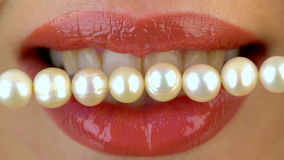 Close up of female lips and pearl bead. Dental concept.