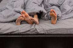 Close up of female and male feet under grey blanket Stock Images
