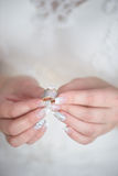 Vertical shot of young Caucasian bride holding a diamond wedding band and an engagement ring with both hands Stock Image
