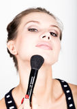 Close-up Female model applying makeup on her face. Beautiful young woman applying foundation on her face with a make up Royalty Free Stock Images