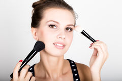 Close-up Female model applying makeup on her face. Beautiful young woman applying foundation on her face with a make up Royalty Free Stock Photo