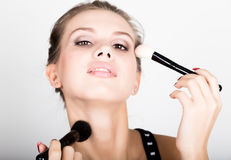 Close-up Female model applying makeup on her face. Beautiful young woman applying foundation on her face with a make up Stock Images