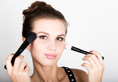 Close-up Female model applying makeup on her face. Beautiful young woman applying foundation on her face with a make up Royalty Free Stock Image