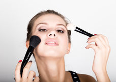 Close-up Female model applying makeup on her face. Beautiful young woman applying foundation on her face with a make up Stock Photos