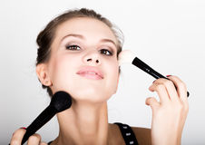 Close-up Female model applying makeup on her face. Beautiful young woman applying foundation on her face with a make up Stock Photo