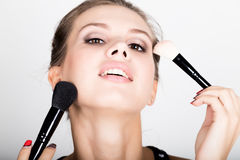 Close-up Female model applying makeup on her face. Beautiful young woman applying foundation on her face with a make up Stock Image