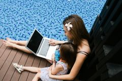 Close-up of female mother, daughter and laptop on background of. Female mother, daughter and laptop keyboard on sunny day background of swimming pool. Family Royalty Free Stock Images