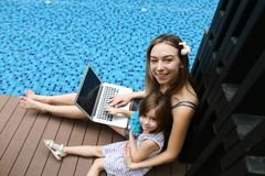 Close-up of female mother, daughter and laptop on background of. Female mother, daughter and laptop keyboard on sunny day background of swimming pool. Family Stock Images