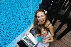 Close-up of female mother, daughter and laptop on background of swimming pool. Female mother, daughter and laptop keyboard on sunny day background of swimming Royalty Free Stock Photos