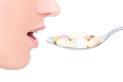 Close up of female mouth and pills on the spoon isolated on whit Royalty Free Stock Photo
