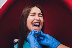 Close up of female mouth with retractor. Doctor flossing the teeth. Dental Gag. Close up of female mouth with retractor. Doctor flossing the teeth. Dental Gag stock images