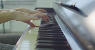 Musician`s hands playing on piano keyboard. Close-up of female musician hands with colorful manicured nails playing on piano keyboard during rehearsal. Artistic stock footage