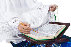Close-up female muslim reading Quran on white Stock Photography