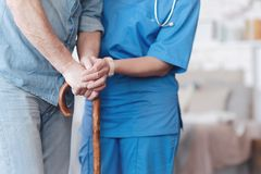 Close up of female nurse helping elderly patient to walk royalty free stock images