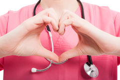 Close-up of female nurse showing heart shape. With hands isolated on white background royalty free stock images