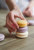 Close up of female pastry chef's hand cooking delicious macaroon. Close up, selective focus Stock Photo