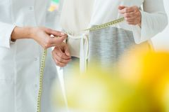 Patient measuring circumference of body. Close-up of female patient and dietician measuring circumference of the body royalty free stock photography
