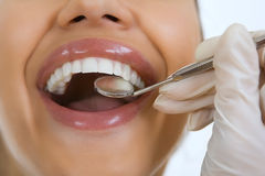 Close-up of female patient having her teeth examined by dentist Stock Image