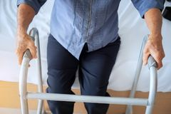 Close-up of female patient moving with walker, Senior woman usin. G a walker in hospital Royalty Free Stock Photo