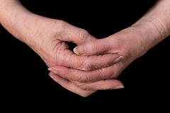 Close up of a female pensioner`s hands loosely clasped. With interlaced fingers, on a black background Stock Image