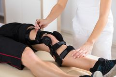 Physiotherapist Giving Leg Exercise. Close-up Of A Female Physiotherapist Giving Leg Exercise In Clinic royalty free stock photography