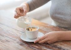 Close up of female pouring milk into coffee Stock Photo