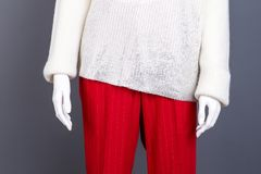 Close up female pullover and trousers. Female mannequin in white knitted sweater and red trousers, cropped image. Feminine stylish outfit Royalty Free Stock Photos