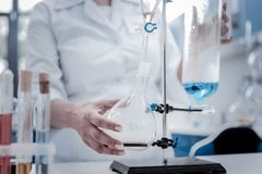 Close up of female researcher working in laboratory. Controlled experiment. Selective focus on a hand of a female chemist wearing a labcoat while holding a flask royalty free stock image