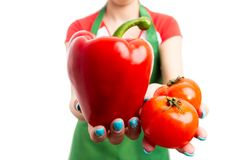 Close-up female retail employee hands holding red vegetables royalty free stock photo