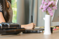 Close-up of female right-hand working on the pen table Royalty Free Stock Photos