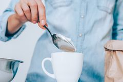 Close-up female`s hand putting spoon of flour in white cup royalty free stock photos