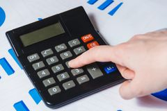 Close-up Of Female`s Hand Using Calculator On Desk with Diagram. Stock Photos
