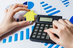 Close-up Of Female`s Hand Using Calculator With Paper House Model On Desk with Diagram. royalty free stock photography