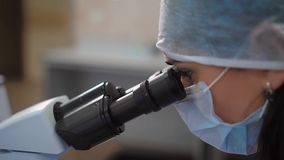 Close up of female scientist in medical protective mask and cap working in research laboratory using microscope. Woman