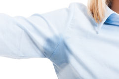 Close-up of female showing arm sweat stains. Close-up of female wearing shirt showing one arm sweat stains isolated on white background royalty free stock photos
