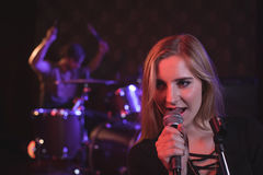 Close up of female singer performing with male drummer. In nightclub Royalty Free Stock Image