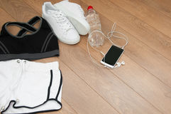 Close up of female sports clothing, sneakers, smartphone, earphones and bottle Stock Photography