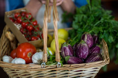 Close-up of female staff holding basket of vegetables in organic section stock images