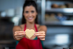 Close-up of female staff showing heart shape cookie at counter. In bake shop royalty free stock image