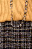 Close up female sweater and skirt. Detail of beige sweater and dark skirt. Women clothes and chain. Female autumn clothing background Royalty Free Stock Image