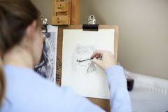 Close Up Of Female Teenage Artist Sitting At Easel Drawing Picture Of Dog From Photograph In Charcoal stock images