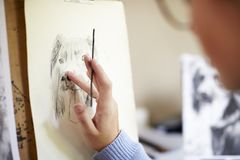 Close Up Of Female Teenage Artist Sitting At Easel Drawing Picture Of Dog From Photograph In Charcoal stock image