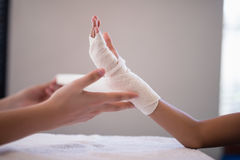 Close-up of female therapist wrapping bandage on hand. At hospital ward Stock Images