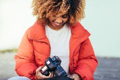 Close up of a female tourist sitting on street with a digital ca. Smiling afro american female sitting outdoors with a dslr camera. Female tourist on vacation royalty free stock photography