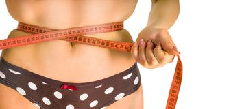Close-up of female tummy and hand holding tape measure arond it royalty free stock photography