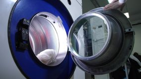Delicate machine wash of blouse in dry cleaning. Close-up of female worker hands loading silk blouse into industry washing machine in dry-cleaning salon stock footage