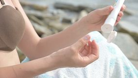 Close-up female young hands on the seashore squeezing sunscreen from a tube. Every summer care concepts. 4k stock video