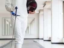 Close-up of a fencer in white fencing suit and holding mask and royalty free stock image
