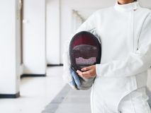 Close-up of a fencer in white fencing suit and holding mask on g stock photo